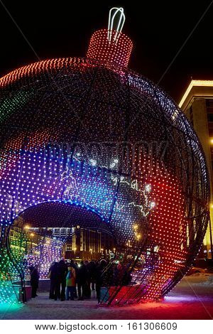 MOSCOW, RUSSIA - JAN 13, 2016: Big fishnet Christmas ball with people inside at Manege Square during New Year holidays in the evening. Manege Square situated near the Kremlin and the Alexander Garden.