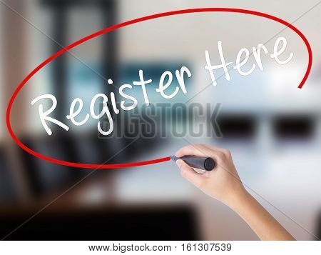 Woman Hand Writing Register Here With A Marker Over Transparent Board