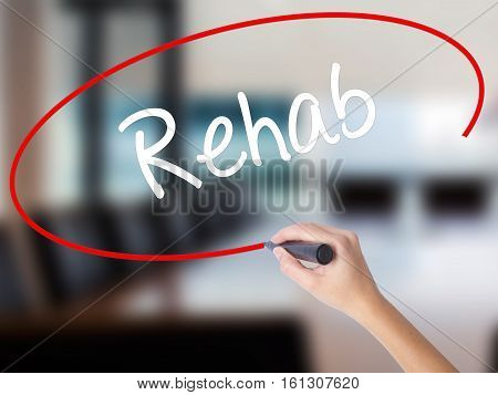 Woman Hand Writing Rehab With A Marker Over Transparent Board
