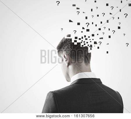 Portrait of man puzzled with questions on light background