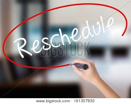 Woman Hand Writing Reschedule  With A Marker Over Transparent Board
