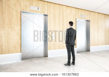Thoughtful businessman in interior with two silver elevators wooden wall concrete floor and ceiling. Choice concept. 3D Rendering