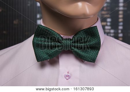 Pink shirt and green bow tie placed on a mannequin