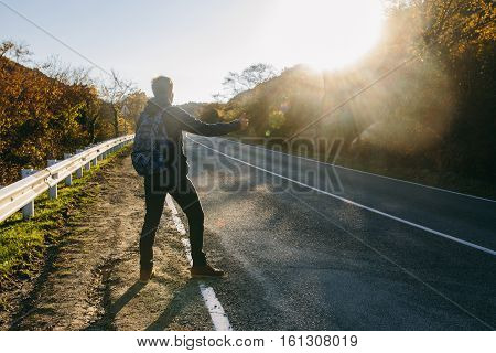 Man hitchhiking on a country road. Traveler showing thumb up on for hitchhiking during road trip. Adventure and tourism concept.