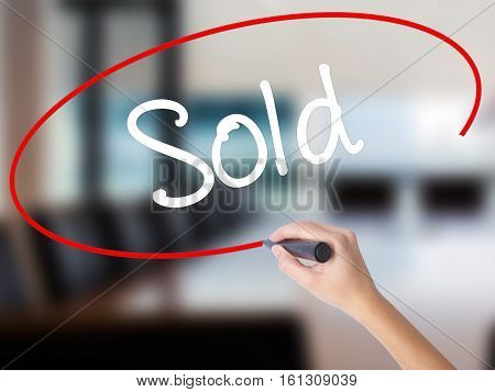 Woman Hand Writing Sold With A Marker Over Transparent Board