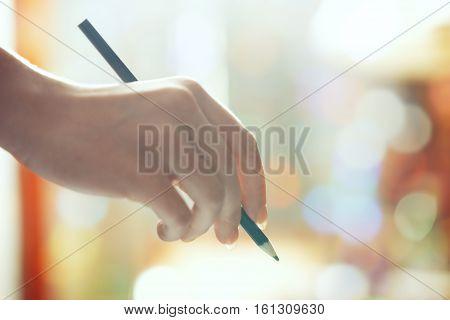 Hand of human holding green pencil. Horizontal photo