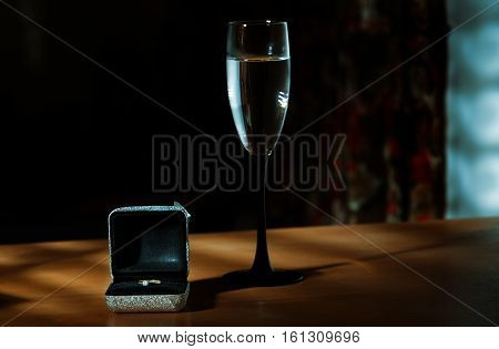 Wedding ring with wine on a table in dark room