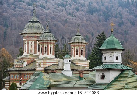 Domes of Sinaia Monastery (Romania Transylvania region) against autumn forest background.