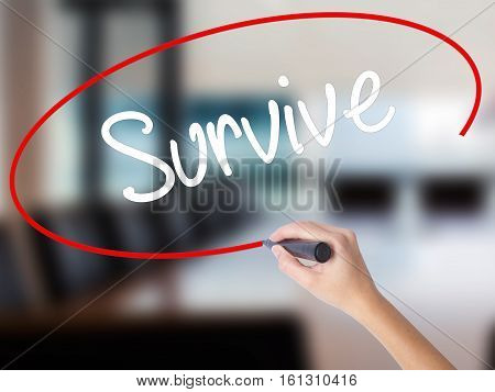 Woman Hand Writing Survive With A Marker Over Transparent Board