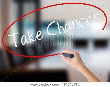 Woman Hand Writing Take Chances With A Marker Over Transparent Board.