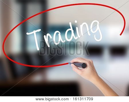 Woman Hand Writing Trading  With A Marker Over Transparent Board