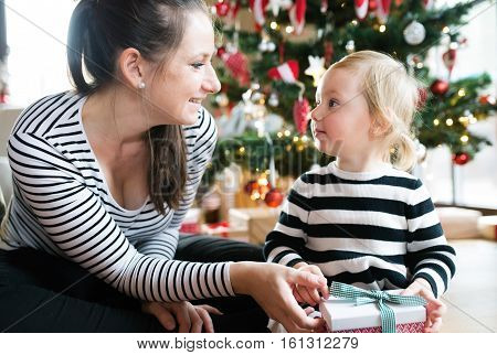 Beautiful young mother giving her cute litte daughter Christmas present at illuminated and decorated Christmas tree.
