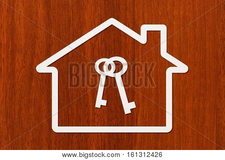 Paper house with keys inside on wooden background. Housing, family concept. Abstract conceptual image