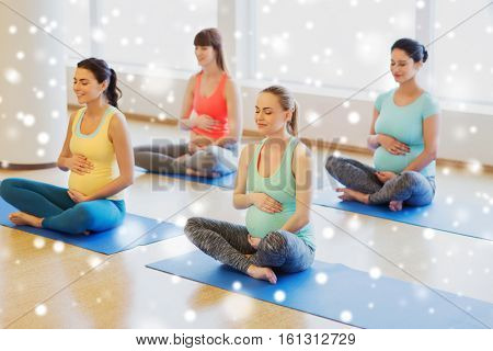 pregnancy, sport, fitness, people and healthy lifestyle concept - group of happy pregnant women exercising yoga and meditating in lotus pose in gym over snow