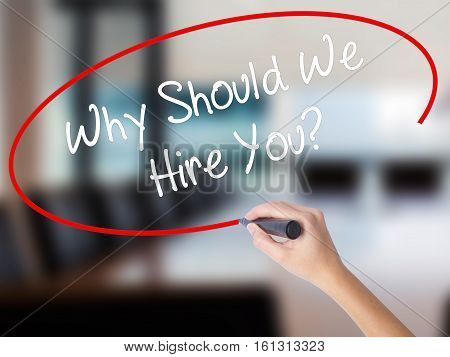 Woman Hand Writing Why Should We Hire You? With A Marker Over Transparent Board