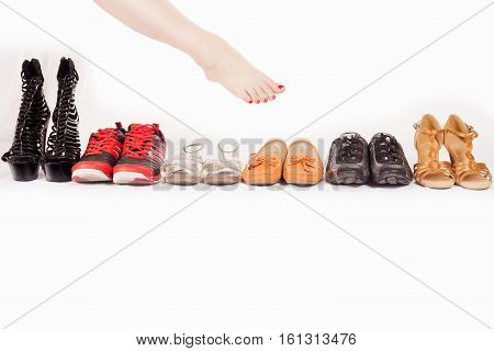 Female leg is choosing shoes on white background shopping concept.