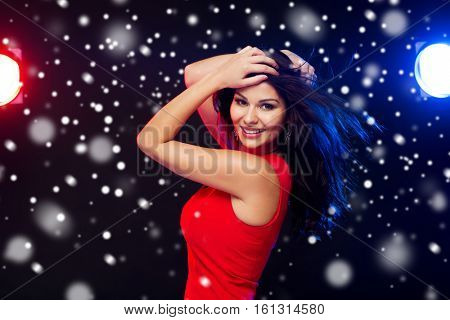 people, winter holidays, disco, night lifestyle and leisure concept - beautiful sexy woman in red dress dancing at nightclub over snow