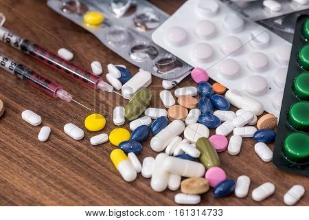 syringe and pills on the table. health concept