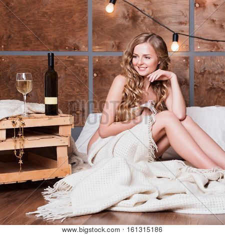 Naked woman wrapped in a blanket with bottle and glass of white wine. Beautiful blonde girl enjoying alcohol. Cozy evening of winter holidays.