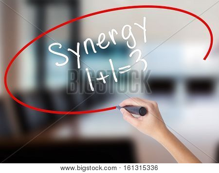 Woman Hand Writing Synergy Concept 1+1=3 With A Marker Over Transparent Board