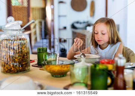 Adorable little girl eating boiled egg for a breakfast in restaurant