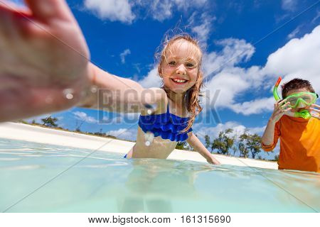 Split underwater and above photo of a little girl having fun in a tropical ocean making selfie