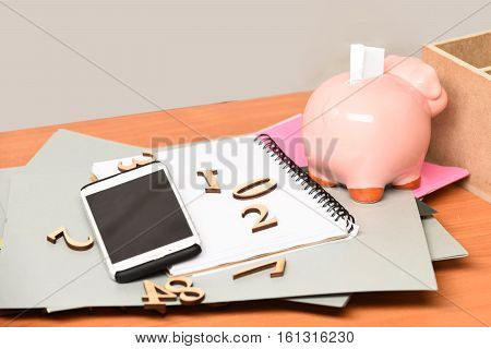 different papers with numbers copybook pink piggy pig bank and cell phone on brown wooden table