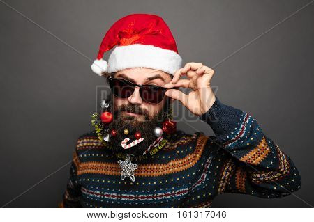 stylish modern Bad Santa concept. Young bearded man wearing sunglasses and santa claus hat. Close up portrait