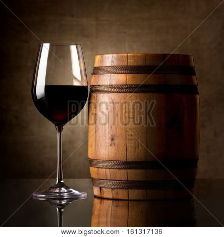 Glass of red wine and a wooden barrel
