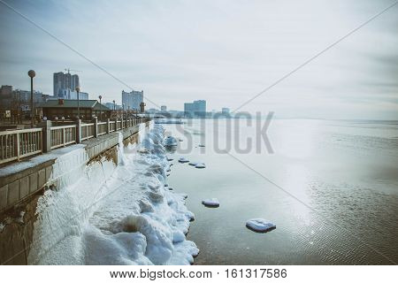 Lighthouse in winter, sea, snow-covered ice on the bay of the city of Vladivostok, Primorye, Russia