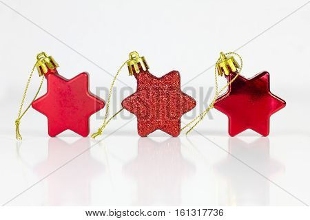 Three christmas red stars over a white background.