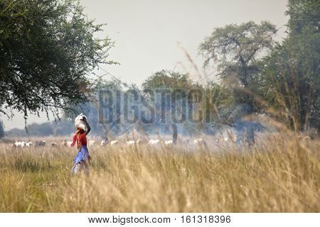 Woman in colorful clothes carrying load on her head in South Sudan