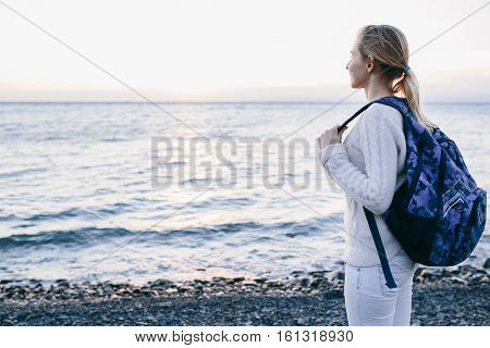 Young woman traveler in a white clothing standing on the shore and looks at sea