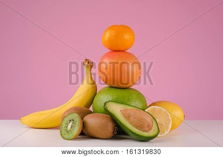 Mixed citrus fruits including lemons, grapefruit, pomelo and tangerines, bananas and avocado on a table isolated on a pink background