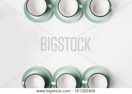 Clean dishes, coffee or tea set frame, background with copy space. Plenty of elegant porcelain light blue cups and saucers at white, high key, top view and flat lay.