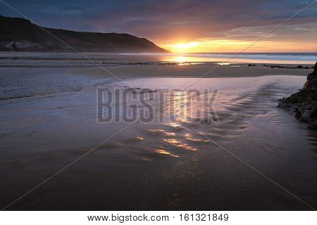 Sunrise over a beach stream at Caswell Bay, one of the most popular and easily accessible beaches on the Gower peninsula in Swansea