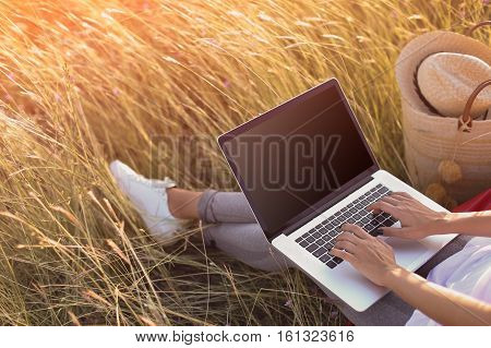 woman typing on a laptop. Empty black screen mockup. Freelancer girl working outdoors. Fashion blogger screen template