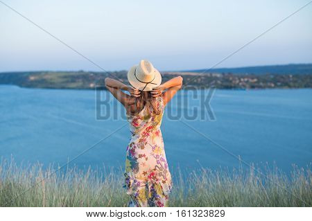 Young girl on cliff at blue lake. Back view of fashion woman in summer floral dress and hat posing outdoors. Inspiration and escape concept