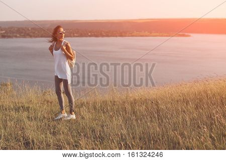 Young traveler with backpack standing on hill near river observing locality. Film filter and orange lens flare