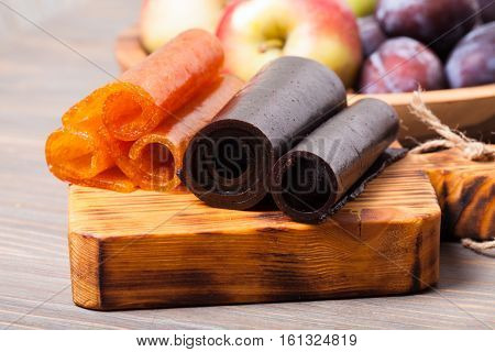 Dry fruit leather on the wooden board, plum and apple