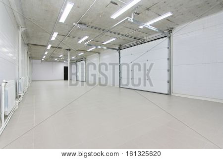 Empty Parking Garage, Warehouse Interior With Large White Gates And Gray Tile Floor
