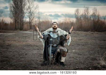 Warrior stood on one knee in the field and raised his hands to the sky.