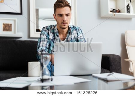 Picture of serious bristle man dressed in shirt in a cage print sitting on sofa in home and using laptop computer. Looking at laptop.