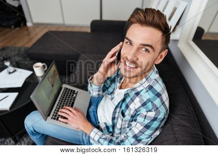 Image of cheerful bristle man dressed in shirt in a cage print sitting on sofa in home and using laptop computer. Looking at the camera while talking by his phone.