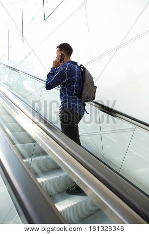 Full body rear angle portrait of man standing on escalator talking on smart phone