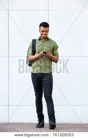 Handsome African Man Standing With Smart Phone And Bag