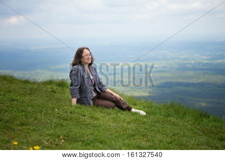 Middle Aged Woman Sitting On The Slope Of Volcano