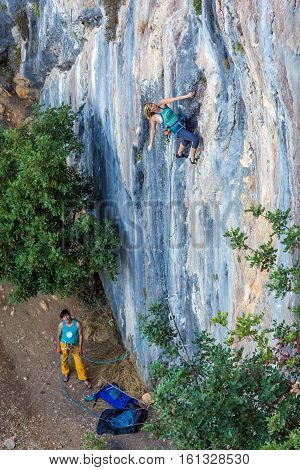 Two Climbers work in pair Female leads Male belays and watch on vertical rocky Wall
