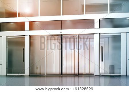 Blank sliding glass doors entrance mockup 3d rendering. Commercial building entry mock up. Office exterior outdoor template. Emporium facade on sunset front view. Sunny shopping center.