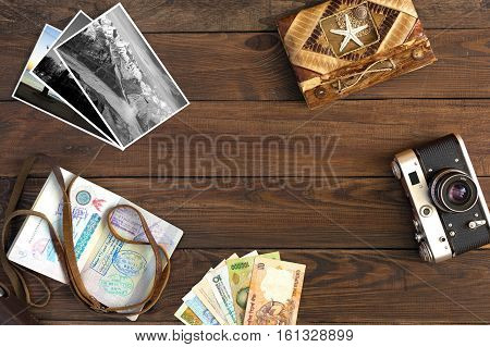 Travel Memories Vintage old Camera exotic Countries Currency Notes handmade Travel Book and opened Passport with many visas entry stamps photo Cards on wood Background